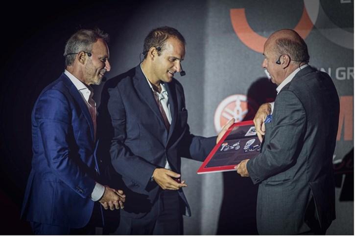 Ο κ. Eric De Seynes, President & CEO της Yamaha Motor Europe παραδίδει την αναμνηστική πλακέτα της  Yamaha Motor Europe για τα 50 χρόνια της ελληνικής αντιπροσωπείας στους  κ.κ. Πάρη Κυριακόπουλο, Πρόεδρο της ΜΟΤΟΔΥΝΑΜΙΚΗΣ,   και Σωτήρη Χατζίκο, Διευθύνοντα Σύμβουλο της ΜΟΤΟΔΥΝΑΜΙΚΗΣ.